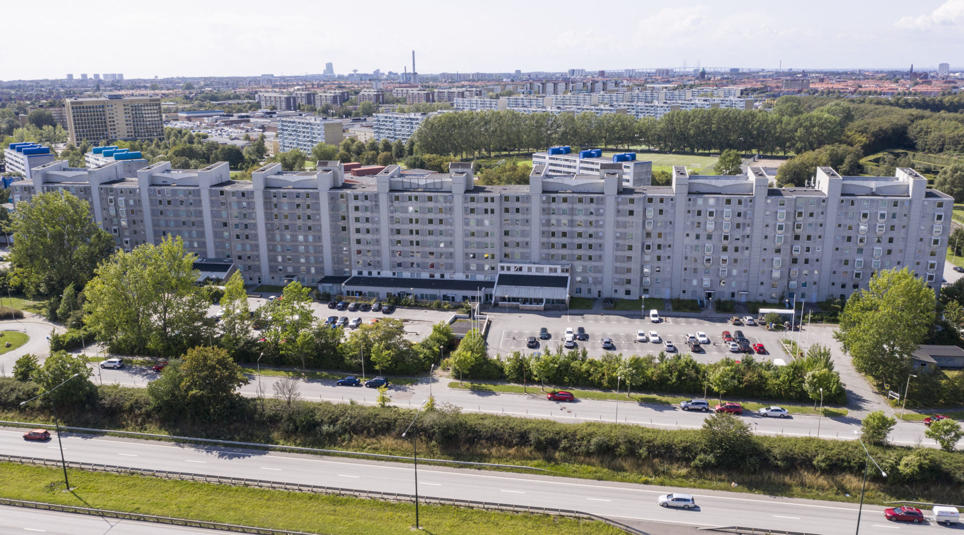 Flygfoto över bostadskomplexet Kinesiska muren i Rosengård, som sträcker sig som en mur utmed vägen.