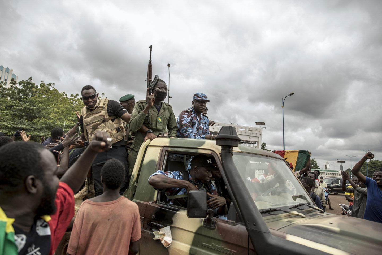 Soldater på flaket till en pickup med vapen i händerna.