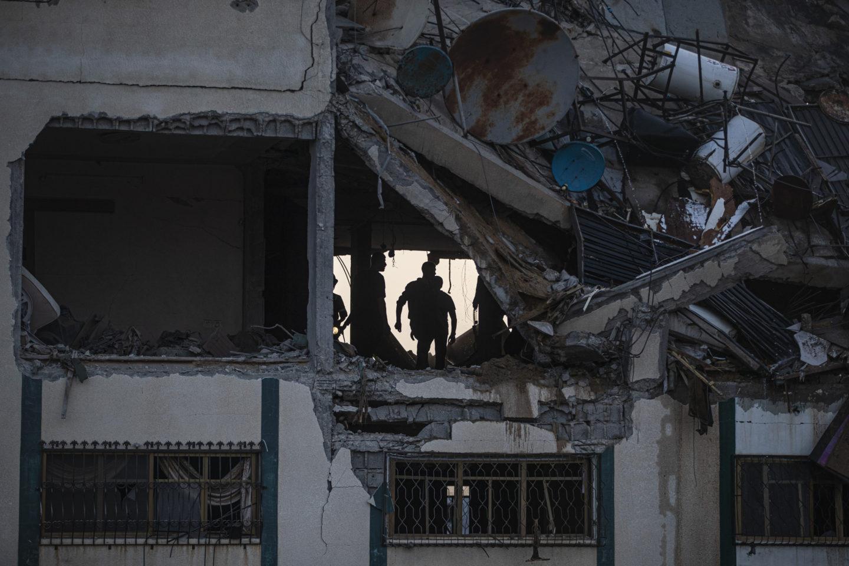 Bombat hus med hål i fasaden och infallet tak. Inne i huset syns människor som söker efter överlevande.
