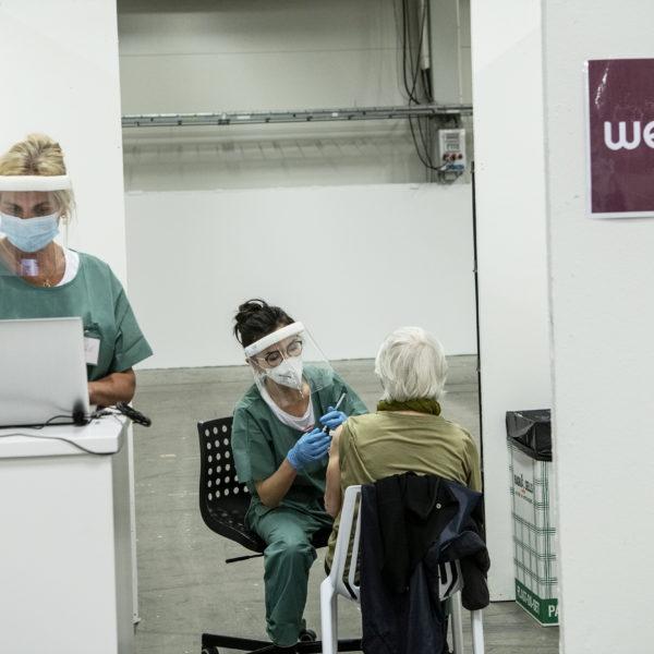 Sjuksköterska står vid en dator, iklädd munskydd och visir. Bakom henne sitter en annan sjuksköterska och vaccinerar en äldre person.