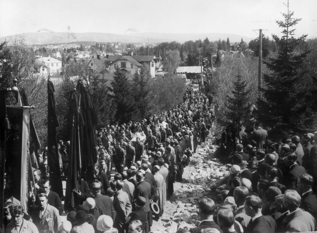 Begravningsföljet efter skotten i Ådalen sträcker sig längs en grankantad väg där många åskådare finns vid vägkanten.