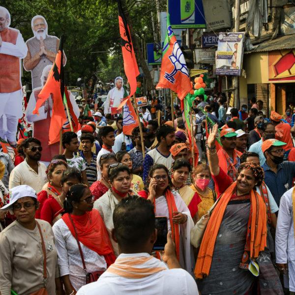 BJP-supportrar med orange sjalar, flaggor och bilder på Narendra Modi går i ett demonstrationståg.