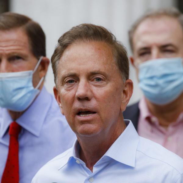 Connecticuts guvernör Ned Lamont tillsammans med två skjortklädda män med munskydd.