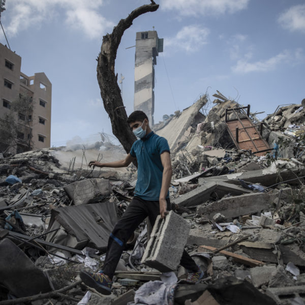 En man går genom de sönderbombade resterna av en flervåningsbyggnad.