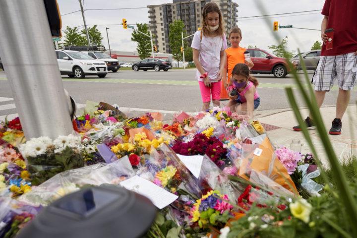 Människor lägger blommor på en trottoar i Kanada
