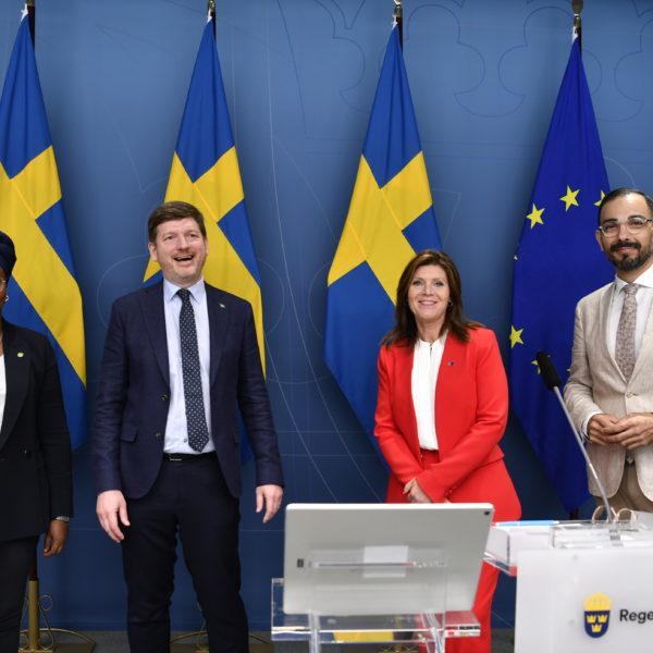 Leila Ali Elmi, arbetsmarknadspolitisk talesperson för (MP), Martin Ådahl, arbetsmarknadspolitisk talesperson (C), abetsmarknadsminister Eva Nordmark och Arman Teimouri, arbetsmarknadspolitisk talesperson för (L), framför svenska flaggor.