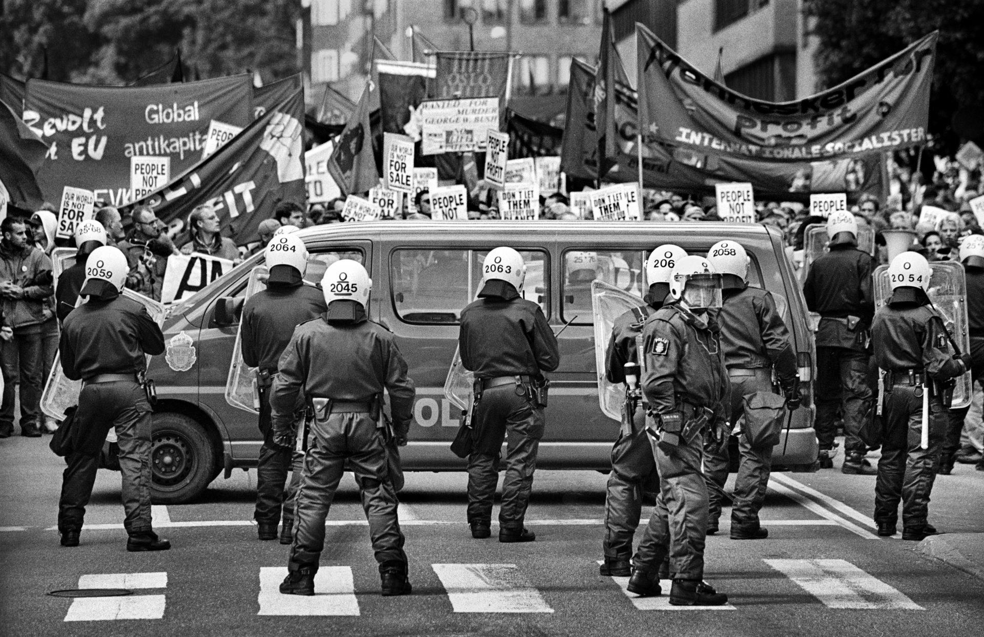 Svartvit bild. Poliser med ryggarna mot kameran. Demonstranter med skyltar och banderoller.