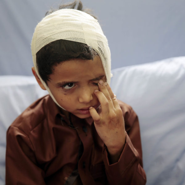 Ett barn i en sjukhussäng, med bandage runt huvudet.