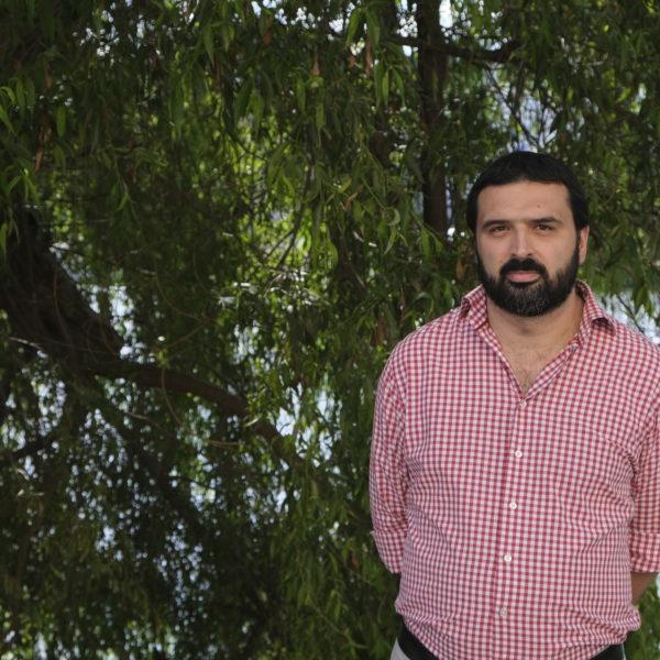Ali Esbati i rödrutig skjorta utomhus.