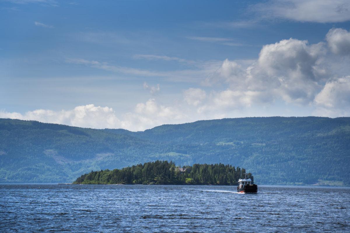 Utøya sedd på avstånd, med berg och himmel i bakgrunden.