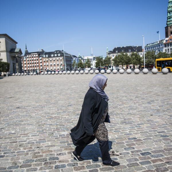 Rihab Kassem går över torget utanför Christiansborg.