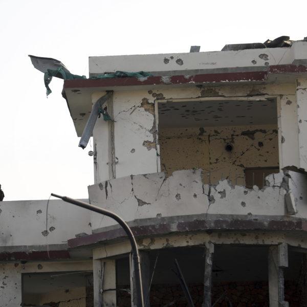 En soldat ståendes på en balkong på ett sönderskjutet hus.