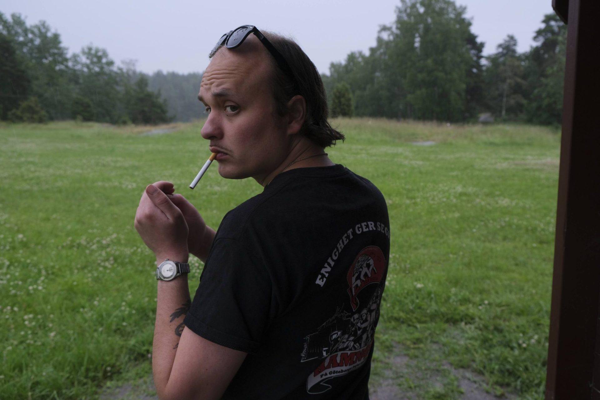 David Ritschard halvt bortvänd, tänder en cigarett.