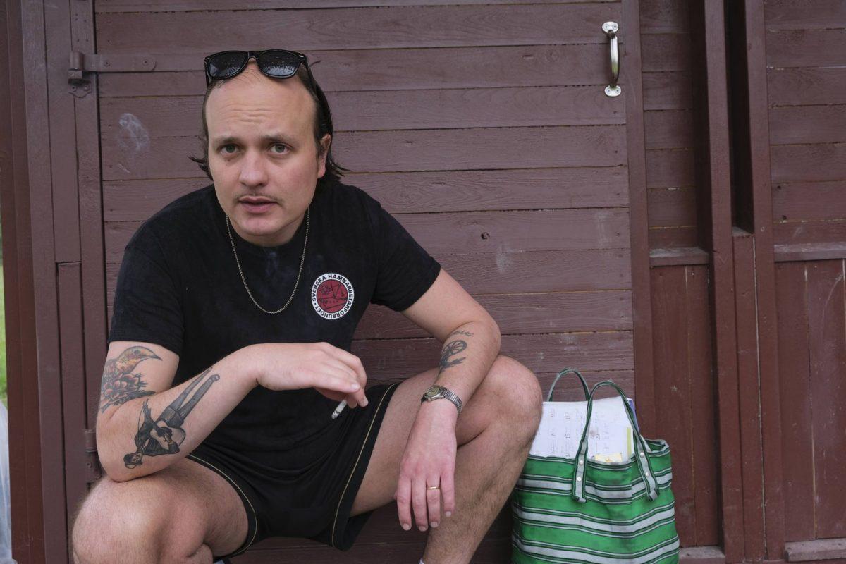 David Ritschard sitter med en cigarett i handen och solglasögon på huvudet.
