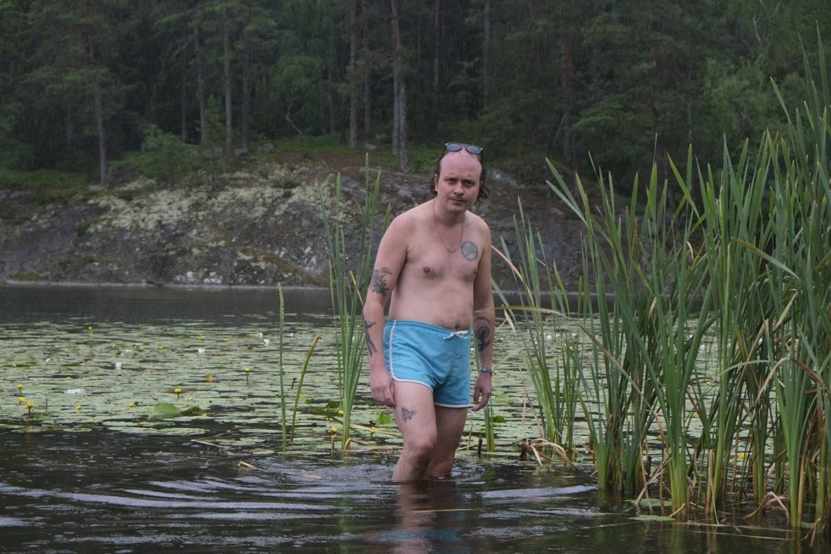 David Ritschard i ljusblå badbyxor ståendes vid vassen i vattnet.