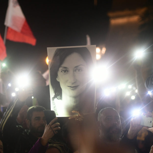 Demonstration i mörker, demonstranter håller upp lysande mobiltelefoner och en bild på den mördade journalisten Daphne Caruana Galizia.