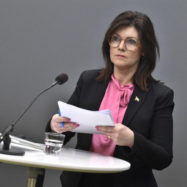 Eva Nordmark på pressträff om arbetslivskriminalitet, ståendes bakom ett högt vitt bord med en mikrofon.