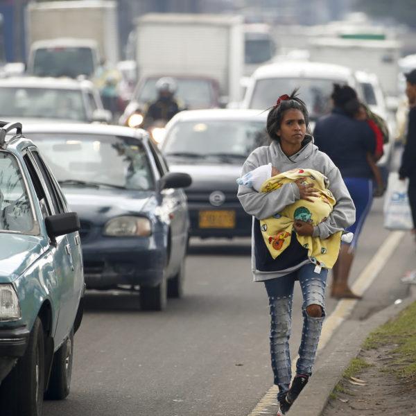 En venezolansk kvinna med ett spädbarn i famnen går längs en väg med bilar i Colombia.