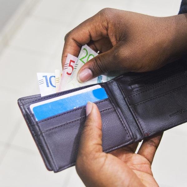 Händer plockar upp sedlar ur en plånbok.