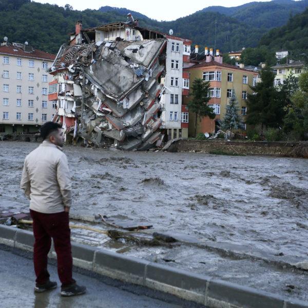 En man ser ut över framvällande vattenmassor. I bakgrunden suns ett raserat hus.