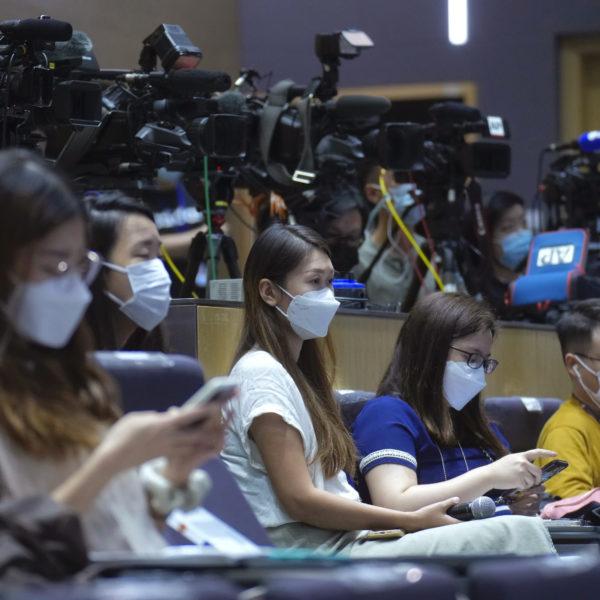 Journalister på en presskonferens framför en rad med kameror.