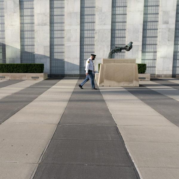 En man passerar utanför FN:s högkvarter. En skulptur av en pistol med pipan ihopknuten till en knut syns.