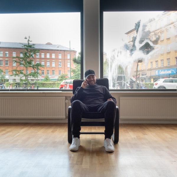 Nicolas Lunabba sittande i en fåtölj i ett tomt rum med utsikt över Möllevången.