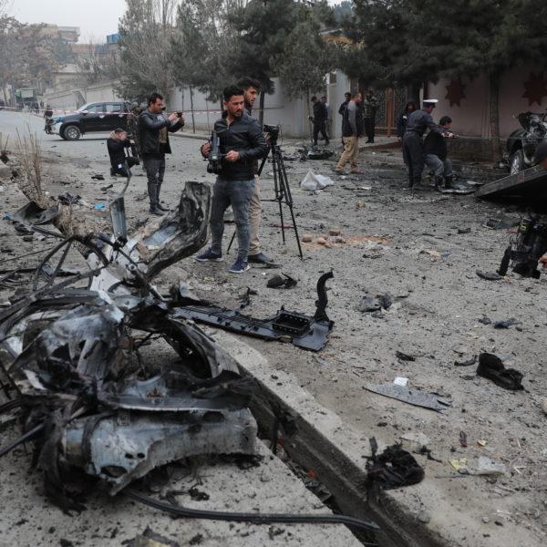 Journalister filmar och fotar på en explosionsplats i Kabul.