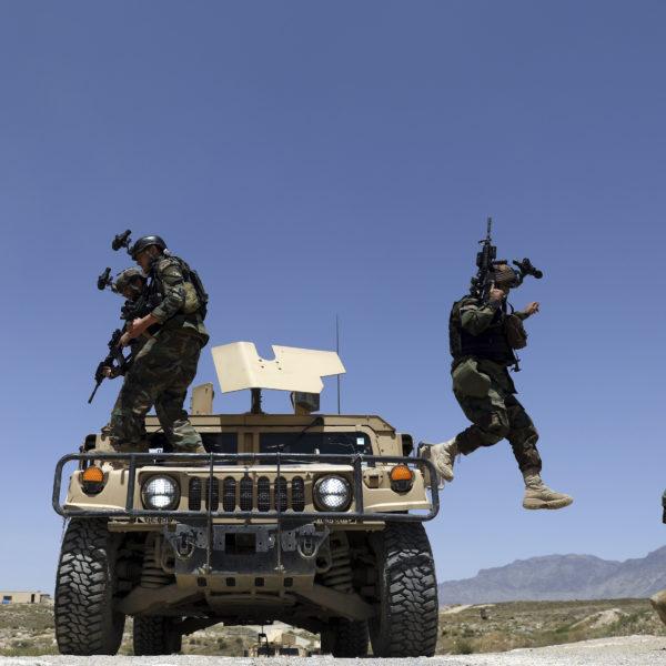 Afghanska soldater med maskingevär och kameror på hjälmarna hoppar ned från ett pansarfordon.