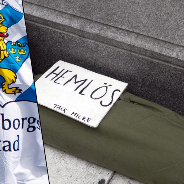 """En flagga med Göteborgs stads stadsvapen bredvid en sovsäck på en gata med en skylt med texten """"Hemlös"""""""