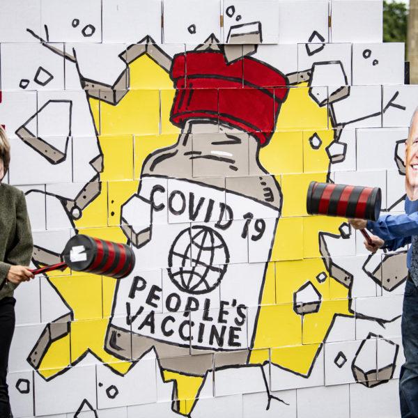 """Aktivister med masker föreställande Angela Merkel och Joe Biden slår med släggor mot en väggmålning där en mur framför en bild av ett """"folkets vaccin"""" krossas."""