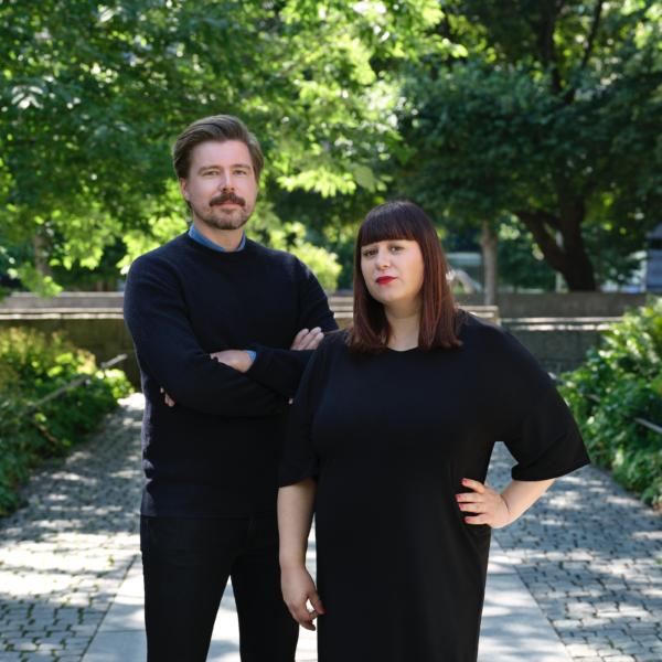 Karl Martinsson och Mira Hjort klädda i svart, utomhus med grönskande träd i bakgrunden.